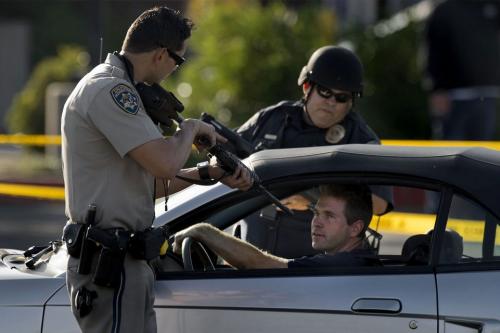 Weisser Polizist zielt mit Waffe auf weissen Fahrzeuglenker